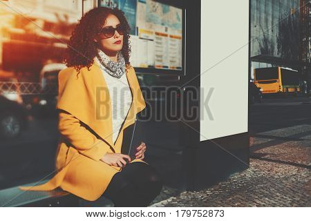 Tired curly beautiful brunette woman in sunglasses and yellow coat holding digital tablet while waiting her bus inside of city bus stop in urban settings with blank mock-up billboard next to her