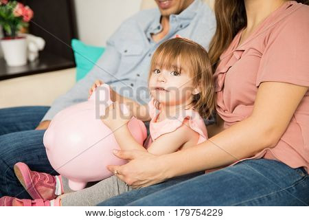 Parents And Daughter Holding A Piggy Bank