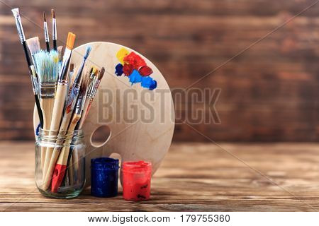 Set of different brushes and acrylic paints to paint scattered on a dark wooden table.Artist workplace background.Art tools.Creativity, visual art concept.Paints brushes and paints palette. Copy space