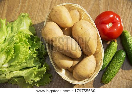 Fresh vegetables. Tomatoes, cucumbers and lettuce on a wooden table. Potatoes in a wicker basket.