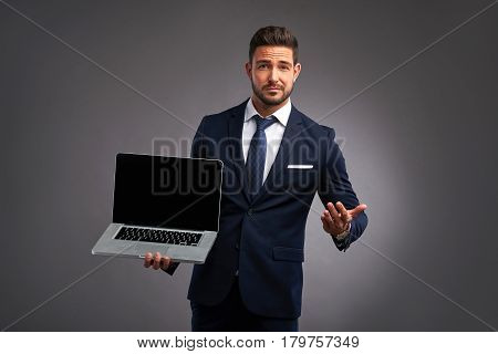 An elegant handsome young man holding and showing the screen of a laptop while looking uncomprehendingly in to the camera