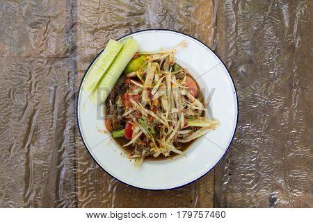 Thai papaya salad (Somtum) on wooden background
