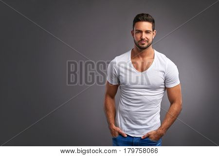 A handsome confident young man standing seriously in a white t-shirt