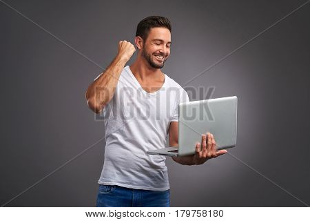 A happy handsome young man holding a laptop and celebrating