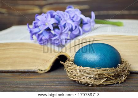 Easter card with blue Easter egg and hyacinth flower on the book