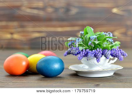 Happy Easter card with colored Easter eggs and spring flowers in tea cup