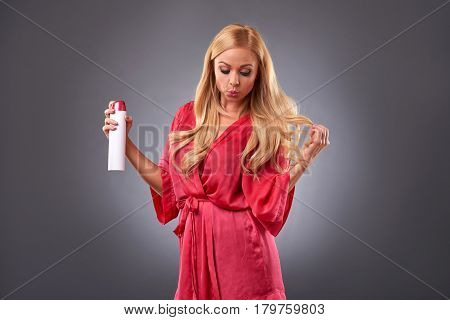 A beautiful young woman wearing a pink robe and smiling while using a hairspray