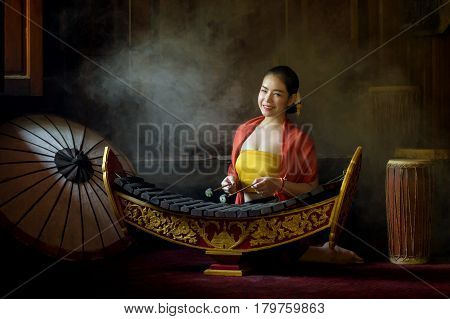 Asian beautiful woman playing xylophone in thailand.