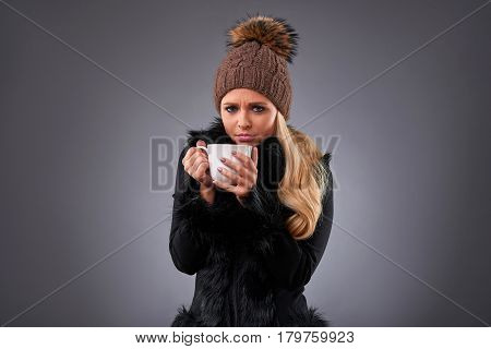 A beautiful young woman standing in an elegant black sweater and a brown hat drinking from a mug while feeling unwell