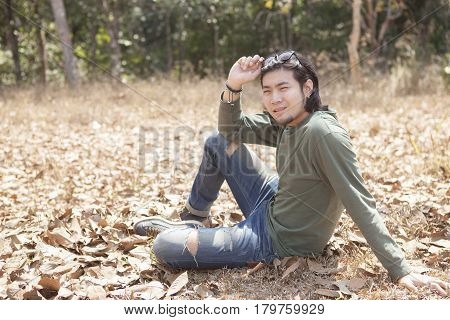 asian younger man sitting on dry leaves field with smiling face
