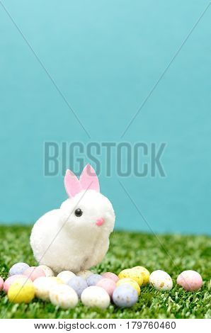 A fluffy bunny figurine with speckled easter eggs