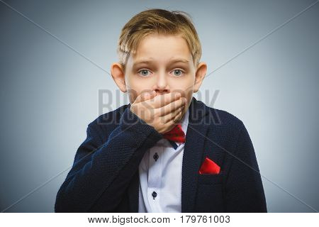 Teenager boy against gray background covering mouth with hand, afraid.