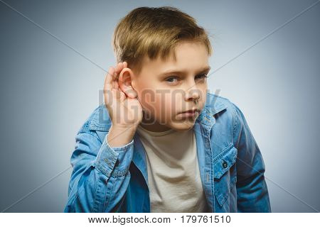 Curious Disappointed boy listens. Closeup portrait child hearing something, parents talk, hand to ear gesture isolated grey background. Human face expression, emotion, body language, life perception.