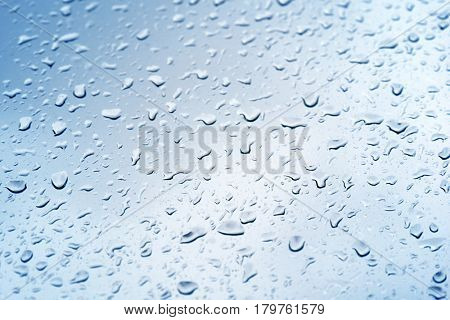 Rain drops cling to glass in window. Blue tone added.