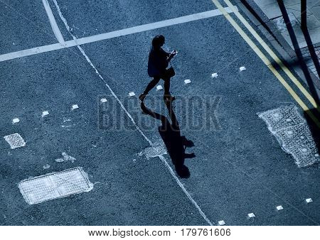 Single woman using computer tablet crossing road at city crossing