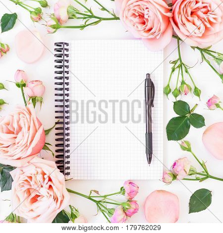 Frame with pink roses, paper notebook and pen on white background. Flat lay, top view. Workspace background.