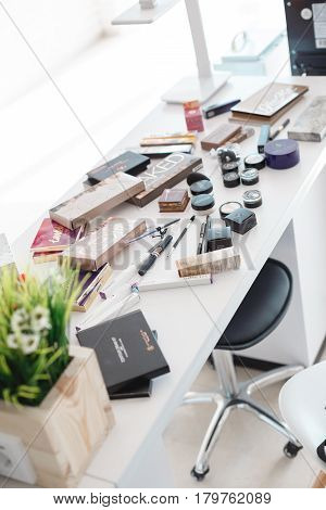 Kyiv, Ukraine - March 3, 2017: Table with decomposition professional cosmetic makeup. Shadows, powder, mascara and lipsticks are on the table.