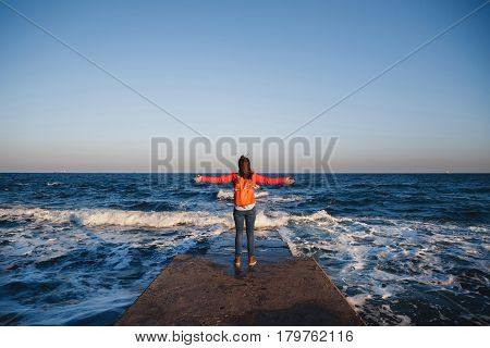 Young happy girl with backpack standing on a seaside breathing fresh air raising arms enjoying the view