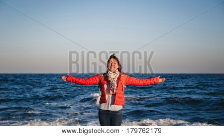 Young happy girl with backpack standing on a seaside breathing fresh air raising arms
