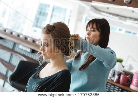 Kyiv, Ukraine - March 3, 2017: Young bride getting her hair done before wedding by professional hair stylist. Stylist at work makes hair to model.