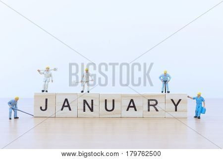 January words with Miniature people worker on wooden floor
