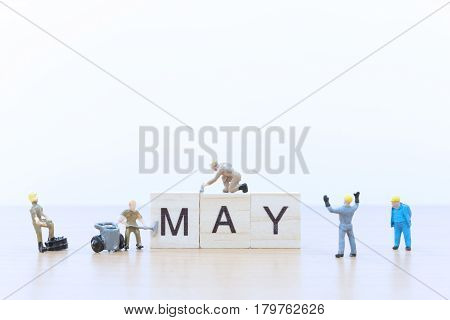 May words with Miniature people worker on wooden floor
