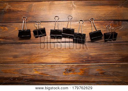 Black clerical paper clips on wooden background.