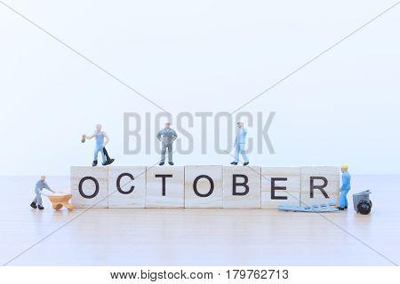October words with Miniature people worker on wooden floor