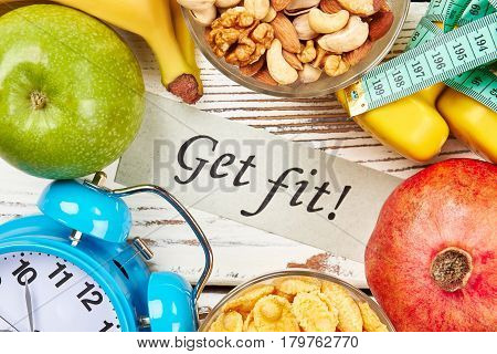 Card, alarm clock and fruits. Good health is above wealth.