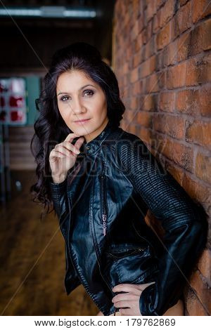 Slender brunette in black leather jacket standing near the wall