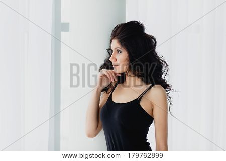 Slender brunette in black little dress standing near a white column