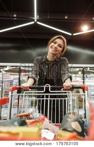 Image of young happy woman in supermarket choosing products with shopping trolley. Looking at camera.