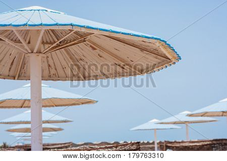 Wooden umbrella on the beach painted blue color
