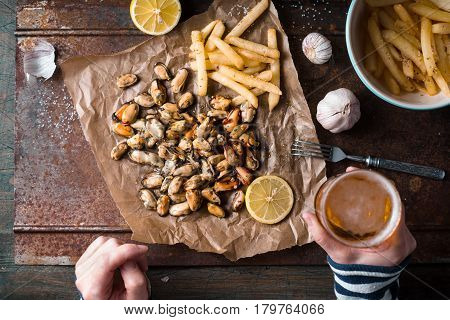 Drinking beer with mussels and French fries top view