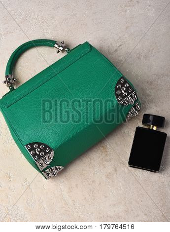 Nice beautiful small womans leather green fashionable bag with decorative metallic spikes or thorns on white textured background near perfume