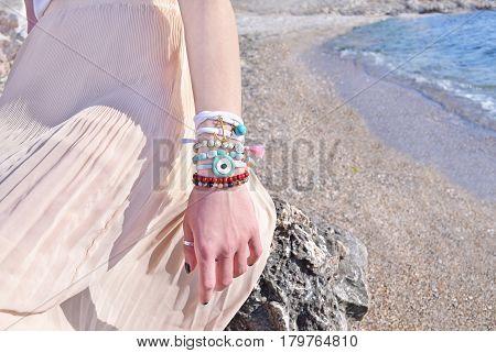 model advertises bohemian greek jewelry on the beach