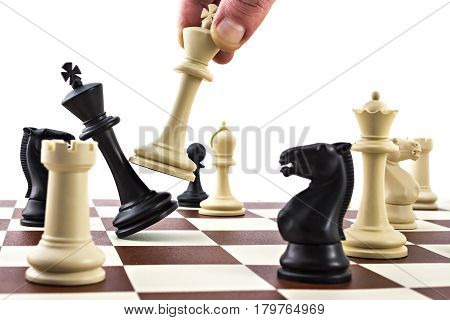 Chess business concept, leader & success. White king is kicking defeated black king on the chess board. Out of the game. Game over