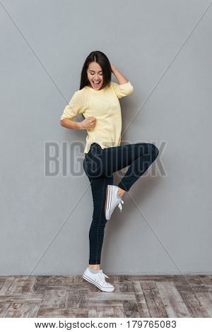 Full length of cheerful attractive young woman dancing and having fun over grey background