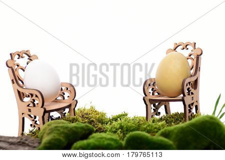 Easter Egg In Wooden Chairs At Table With Green Moss