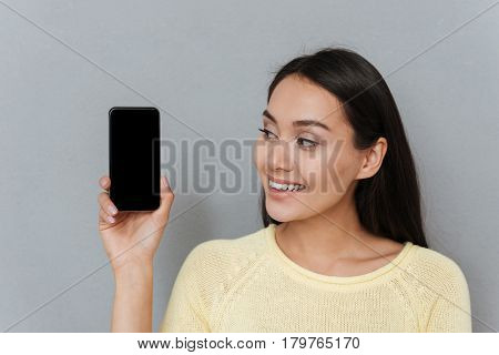 Portrait of smiling pretty young woman with blank screen smartphone over grey background