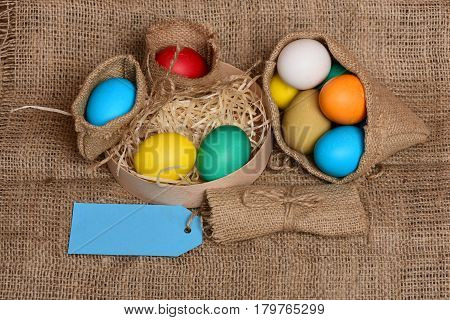 Easter Colorful Eggs In Burlap Sack And Box With Tag