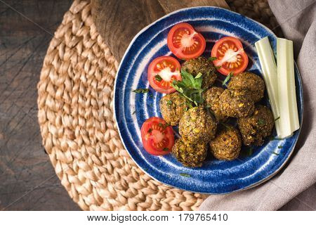 Falafel with tomatoes in the ceramic plate top view