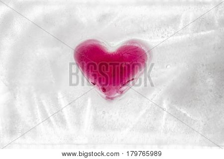 Red crystal heart frozen in a block of ice, on white background. Valentine's day