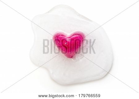 Red crystal heart frozen frozen in a melting block of ice, on white background. Valentine's day