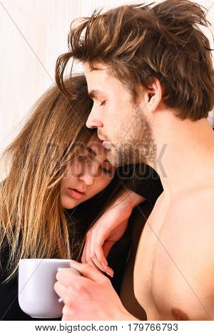 couple of pretty cute brunette girl in black bodysuit and bearded caucasian man with moustache show muscle torso on athletic body holding cup or mug on white wooden studio background