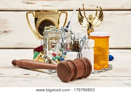 Chain, pills, hammer and awards. Doping scandal and verdict.
