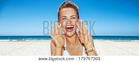 Woman Shouting Through Megaphone Shaped Hands At Sandy Beach