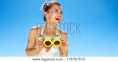 Smiling Woman At Sandy Beach Holding Funky Pineapple Glasses