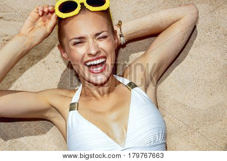 Smiling Woman In Pineapple Glasses Laying On Sand And Winking