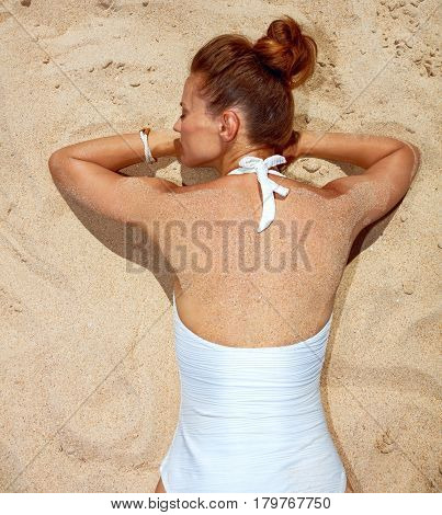 Seen From Behind Woman In Swimsuit Laying On The Sand